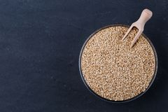 Quinoa seeds in glass bowl from above. White Sesame seeds in glass bowl on darck background top view, space for text. Vegan protein source. Superfoods and stock photos