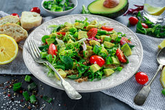 Quinoa tabbouleh salad with avocado, tomatoes, cucumber, green onion. Concept healthy food. Royalty Free Stock Photography
