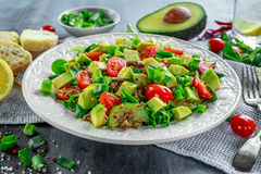 Quinoa tabbouleh salad with avocado, tomatoes, cucumber, green onion. Concept healthy food. Royalty Free Stock Photo