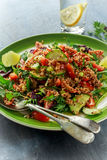 Quinoa tabbouleh salad with tomatoes, cucumber green onion. Concept healthy food Stock Images