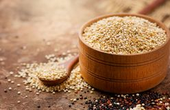 Quinoa. White quinoa grains in a wooden bowl. Healthy food. Seeds of white, red and black quinoa - Chenopodium qu Royalty Free Stock Photos