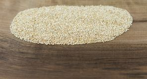 Quinoa on wooden board. Close up view Royalty Free Stock Images