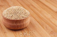 Quinoa in wooden bowl on brown bamboo board, close up. Healthy dietary groats  background Royalty Free Stock Photo