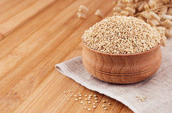 Quinoa in wooden bowl on brown bamboo board, close up. Rustic style, healthy dietary groats background. Stock Image