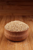 Quinoa in wooden bowl on brown bamboo board, close up. Rustic style, healthy dietary groats  background. Royalty Free Stock Photo