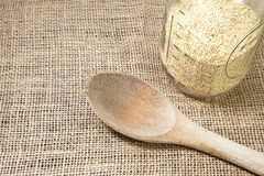 Quinoa and wooden spoon with burlap background-con. A wooden spoon with quino and jar on a burlap background-concept Stock Photos