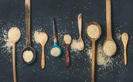 Quinoa zaden in verschillende lepels over zwarte steenachtergrond Royalty-vrije Stock Fotografie
