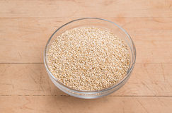 Quinoaen kärnar ur i en glass bunke på en stressad träbakgrund Arkivfoton