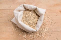 Quinoaen kärnar ur i en kräm- tygpåse på en stressad träbakgrund Royaltyfri Bild