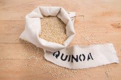 Quinoaen kärnar ur i en kräm- tygpåse på en stressad träbakgrund Arkivfoto