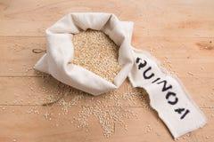 Quinoaen kärnar ur i en kräm- tygpåse på en stressad träbakgrund Royaltyfri Foto