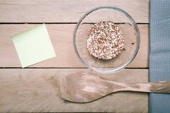 Quinoakorn och matlagning skedar, gulnar anmärkningen Royaltyfri Foto
