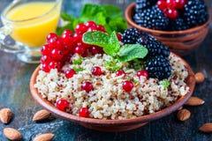 Quinoasallad med bär, mintkaramellen och valnötter på en mörk träbakgrund Superfoods rengöring som äter begrepp Arkivfoto