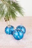 Quinquilharias azuis do Natal nos flocos de neve e no ramo de pinheiro Fotografia de Stock