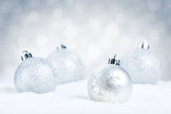 Quinquilharias de prata do Natal na neve com um fundo de prata Fotografia de Stock Royalty Free