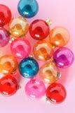 Quinquilharias de vidro translúcidas coloridas do Natal no fundo cor-de-rosa Vista superior Fotografia de Stock Royalty Free