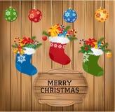 Quinquilharias do Natal e avivar com ramo do abeto, bastão de doces e presentes no fundo de madeira com Christmasgreetings alegre Imagens de Stock