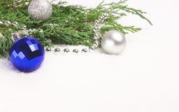 Quinquilharias do Natal e ramos sempre-verdes no branco imagens de stock