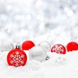 Quinquilharias do Natal na neve com fundo de prata Fotos de Stock Royalty Free