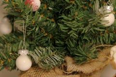 Quinquilharias minúsculas do White Christmas que penduram em uma árvore de Natal diminuta fotos de stock royalty free