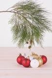 Quinquilharias vermelhas, do branco e do ouro do Natal e ramo de pinheiro Foto de Stock