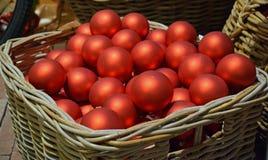 Quinquilharias vermelhas do Natal em uma cesta da precipitação Fotografia de Stock Royalty Free