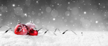 Quinquilharias vermelhas na neve com estrelas efervescentes Imagem de Stock