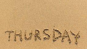 Quinta-feira - palavra tirada na areia amarela brilhante da praia Sumário Imagem de Stock