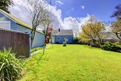 Quintal com a casa azul pequena e grama verde-clara da mola. Imagem de Stock Royalty Free