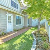 Quintal quadrado de uma casa com o caminho do tijolo e o gramado verde rico vistos em um dia ensolarado imagens de stock