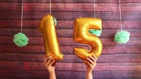 Quinze aniversário feliz, balões de ar dourados com número 15, celebração do aniversário com decorações video estoque