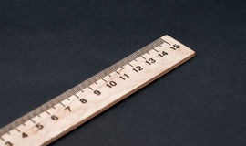 Quinze cm Taille normale Règle en bois sur un fond noir Règle simple Fond de conseil pédagogique Photo stock