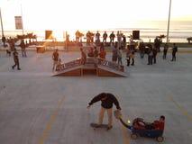 Quiosco en el cielo púrpura de la puesta del sol nublada en el torneo del patín del puerto marítimo de la playa de la belleza Foto de archivo