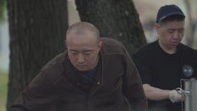 Quiosque asiático do fast food da rua no parque da cidade, frigideira chinesa cozinhando grande do metal filme