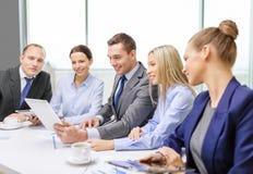 Équipe d'affaires avec le PC de comprimé ayant la discussion Image stock