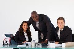 Équipe d'affaires dans un bureau souriant à l'appareil-photo Photos libres de droits