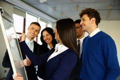Équipe heureuse d'affaires avec le conseil de secousse Photo stock