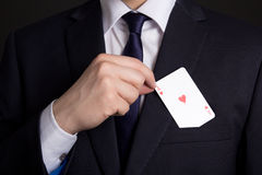 Équipe la main se cachant jouant la carte dans la poche de costume Photographie stock libre de droits