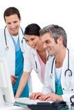 Équipe médicale joyeuse travaillant à un ordinateur Photo stock