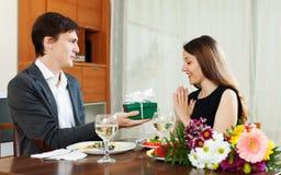 Équipez donner actuel à la jeune femme pendant le dîner romantique Images libres de droits
