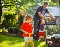 Équipez et deux petits garçons d'enfant de mêmes parents ayant l'amusement avec la tondeuse à gazon Image libre de droits