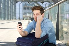 Équipez l'attente à l'aéroport avec l'expression ennuyée sur le visage Photographie stock
