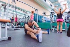 Équipez l'étirage et les femmes faisant des exercices d'haltères dans le gymnase Photographie stock