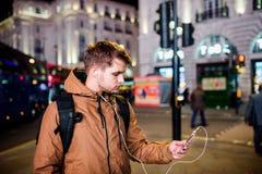 Équipez la marche dans les rues de Londres la nuit Photographie stock libre de droits