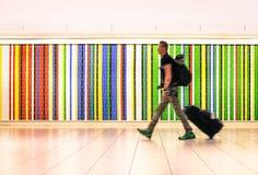 Équipez la marche à l'aéroport international avec la valise de voyage Photo stock