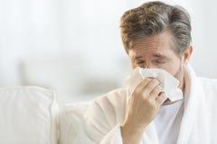 Équipez le nez de soufflement dans le mouchoir Images stock