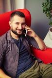 Équipez le repos sur la chaise et parler au téléphone Photos libres de droits
