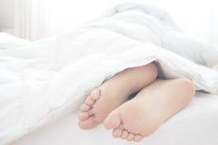 Équipez le sommeil en montrant ses pieds sous l'édredon Photos libres de droits