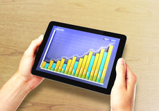 Équipez les mains avec le comprimé numérique avec le graphique de gestion sur le bureau Images libres de droits