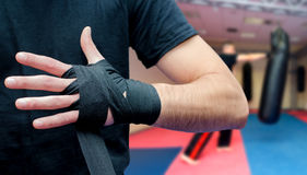 Équipez mettre des bandages sur des mains avant des arts de maréchal s'exerçant dans s Photos stock